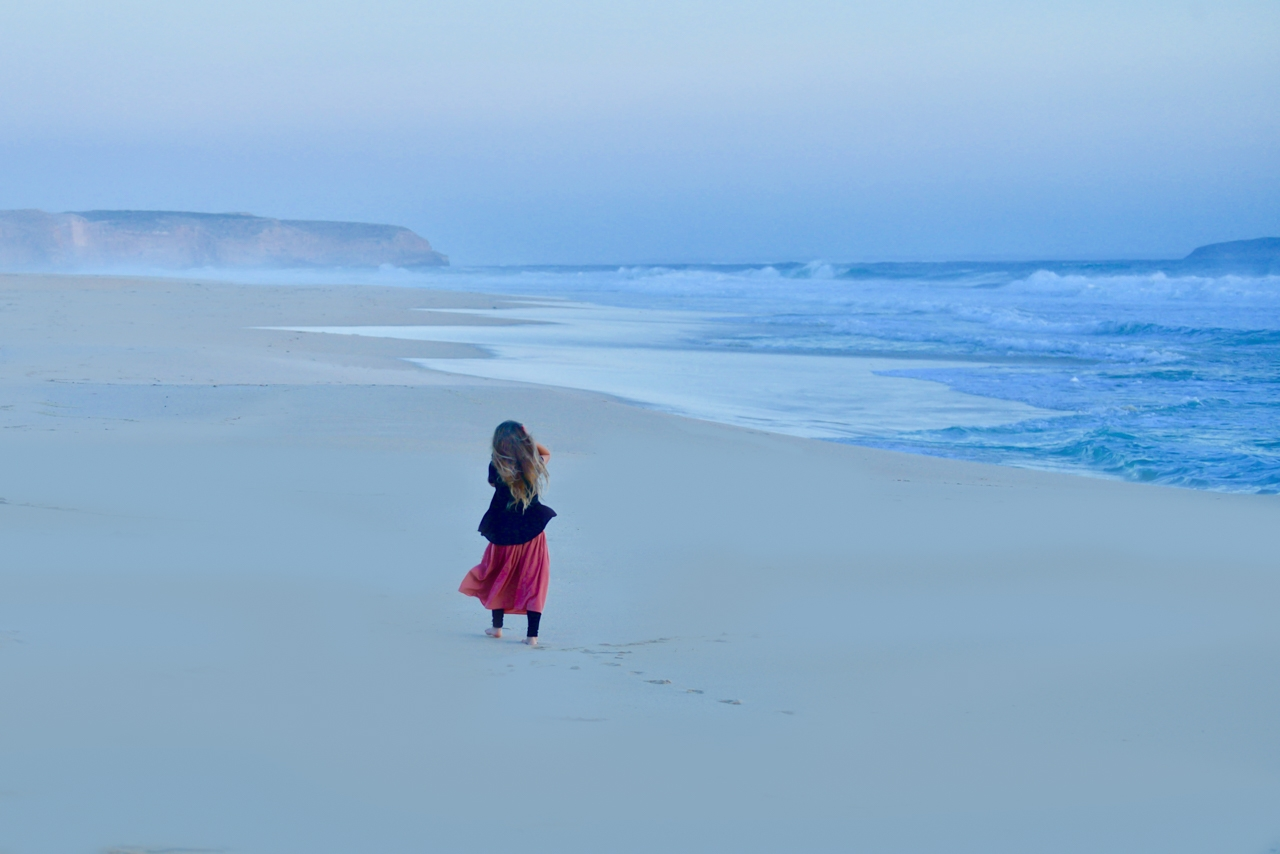Girl-in-red-skirt-walks-along-beach
